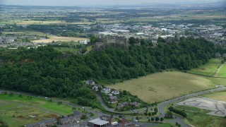 AX109_022 - 6K stock footage aerial video approach Stirling Castle among tree covered hillside, Scotland
