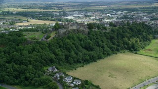 AX109_023 - 6K stock footage aerial video of an approach to Stirling Castle on a tree covered hillside, Scotland