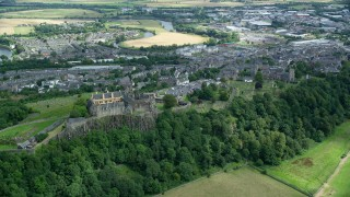 AX109_037 - 6K stock footage aerial video of Stirling Castle on a tree covered hill, Scotland