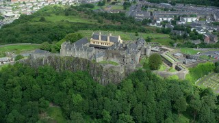 AX109_038 - 6K stock footage aerial video of passing Stirling Castle atop a tree covered hill, Scotland