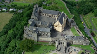 AX109_040 - 6K stock footage aerial video orbiting historic Stirling Castle with tourists, Scotland