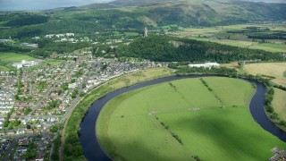 AX109_045 - 6K stock footage aerial video of approaching historic Wallace Monument bordered by residential area, Scotland