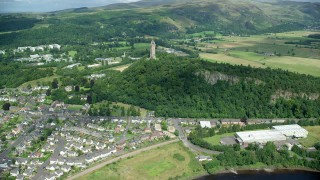 AX109_047 - 6K stock footage aerial video of approaching the historic Wallace Monument surrounded by trees, Stirling, Scotland