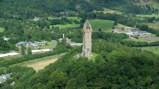 AX109_048 - 6K stock footage aerial video of Wallace Monument and hilltop trees, Stirling, Scotland