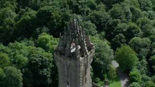 AX109_052 - 6K stock footage aerial video of orbiting top of historic Wallace Monument among trees, Stirling, Scotland