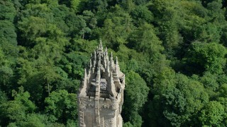 AX109_053 - 6K stock footage aerial video of orbiting top of iconic Wallace Monument surrounded in trees, Stirling, Scotland