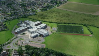 AX109_054 - 6K stock footage aerial video of orbiting Wallace High School and soccer field, Stirling, Scotland
