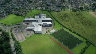 AX109_055 - 6K stock footage aerial video of orbiting Wallace High School and soccer field, Stirling, Scotland