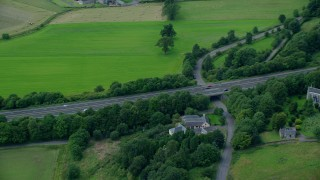 AX109_058 - 6K stock footage aerial video of M9 Highway lined with trees, Stirling, Scotland