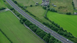 AX109_059 - 6K stock footage aerial video of M9 Highway through green farmland, Stirling, Scotland