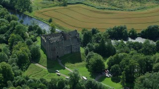 AX109_067 - 6K stock footage aerial video of orbiting Doune Castle with trees, Scotland