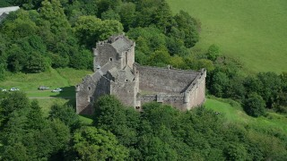 AX109_070 - 6K stock footage aerial video of orbiting iconic Doune Castle nestled in trees, Scotland