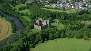 AX109_074 - 6K stock footage aerial video of iconic Doune Castle with trees along a river, Scotland