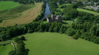 AX109_075 - 6K stock footage aerial video of Doune Castle and River Teith among trees, Scotland