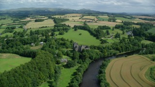 AX109_087 - 6K stock footage aerial video of flying over historic Doune Castle toward farmland, Scotland
