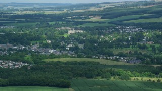 AX109_092 - 6K stock footage aerial video of small town surrounded by green countryside, Dunblane Scotland