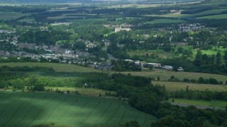 AX109_093 - 6K stock footage aerial video of small town surrounded by countryside, Dunblane, Scotland