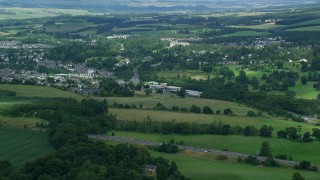 AX109_094 - 6K stock footage aerial video of a town surrounded by countryside, Dunblane, Scotland