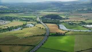 AX109_095 - 6K stock footage aerial video of M9 highway and farmland, Stirling, Scotland