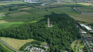 AX109_099 - 6K stock footage aerial video of approaching Wallace Monument surrounded by trees, Stirling, Scotland