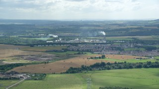 AX109_107 - 6K stock footage aerial video of factory and smoke stacks in a small town, Cowie, Scotland