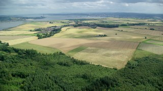 AX109_110 - 6K stock footage aerial video tilt from forest to farm fields by Airth, Scotland