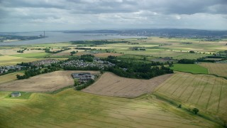 AX109_112 - 6K stock footage aerial video approach homes and farm fields in Scottish village, Airth, Scotland