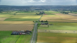 AX109_114 - 6K stock footage aerial video of a roundabout on the A905 highway through farmland, Falkirk, Scotland