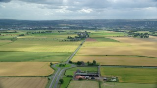 AX109_115 - 6K stock footage aerial video fly over roundabout on A905 highway by farm fields, Falkirk, Scotland