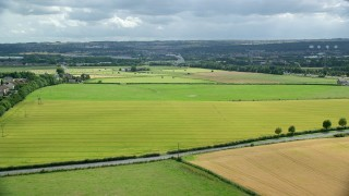 AX109_118 - 6K stock footage aerial video of green Scottish farm fields seen while approaching The Kelpies, Falkirk, Scotland