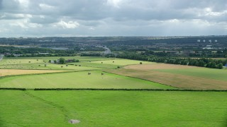 AX109_119 - 6K stock footage aerial video fly over Scottish farm fields toward The Kelpies sculptures, Falkirk, Scotland