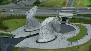 AX109_127 - 6K stock footage aerial video of circling The Kelpies sculptures with tourists in Falkirk, Scotland
