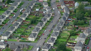 AX109_135 - 6K stock footage aerial video of town houses in a Scottish neighborhood, Falkirk, Scotland