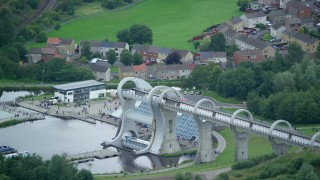 AX109_164 - 6K stock footage aerial video of a reverse view of the Falkirk Wheel boat lift with homes in the background, Scotland