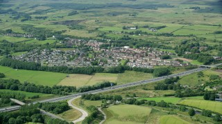 AX109_172 - 6K stock footage aerial video of farm fields and highway M80 by rural village homes, Bonnybridge, Scotland
