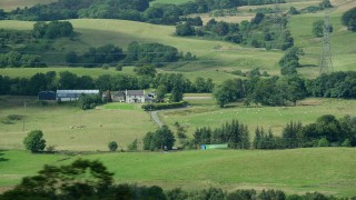 AX109_177 - 6K stock footage aerial video of passing by a sheep farm in Cumbernauld, Scotland