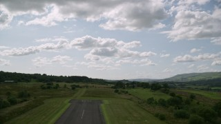AX110_001 - 6K stock footage aerial video of taking off from Cumbernauld Airport, Scotland