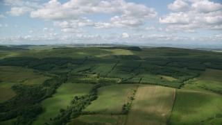 AX110_003 - 6K stock footage aerial video approach farm field and forests, Banton, Scotland