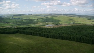 AX110_006 - 6K stock footage aerial video approach forest, reveal Buckleburn Reservoir and countryside, Denny, Scotland