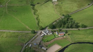 AX110_009 - 6K stock footage aerial video of a farm with green fields, Denny, Scotland