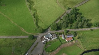 AX110_010 - 6K stock footage aerial video tilt to bird's eye of a farm with green fields in Denny, Scotland