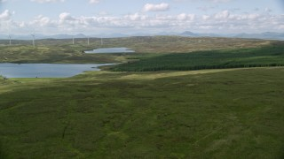 AX110_017 - 6K stock footage aerial video approach Earlsburn Reservoirs and forest in Scotland