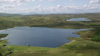 AX110_018 - 6K stock footage aerial video approach Earlsburn Reservoirs and windmills, Scotland