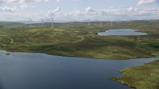 AX110_019 - 6K stock footage aerial video fly over Earlsburn Reservoirs by windmills, Scotland