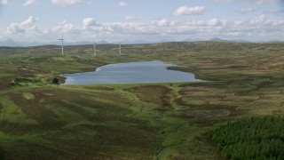 AX110_020 - 6K stock footage aerial video approach Earlsburn Reservoir 2 and windmills, Scotland