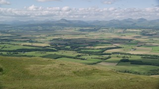 AX110_027 - 6K stock footage aerial video fly over hills to approach Carleatheran, reveal farm fields, Scotland
