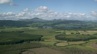 AX110_037 - 6K stock footage aerial video of Lake of Menteith, forests, mountains, Scotland