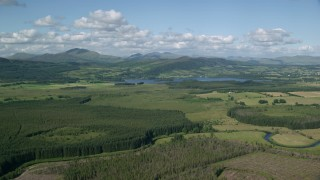 AX110_038 - 6K stock footage aerial video of Lake of Menteith by forests and mountains, Scotland