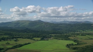AX110_040 - 6K stock footage aerial video of Scottish forest, farmland and mountains, Aberfoyle, Scotland