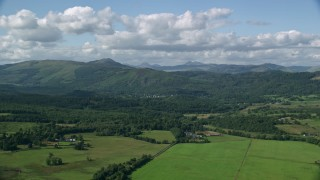 AX110_041 - 6K aerial stock footage video of farms, forest and mountains near Aberfoyle, Scotland
